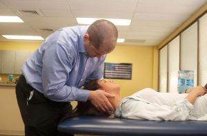 Jeff Woods with neck patient at Optimum Performance Physical Therapy